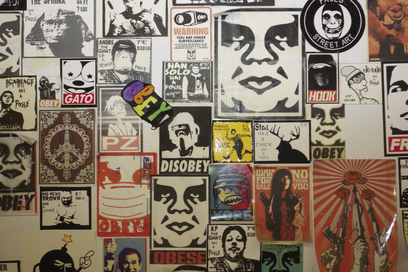 """and a close-up of sticker graffiti in a public bathroom, including Fairey's """"Obey Giant."""""""