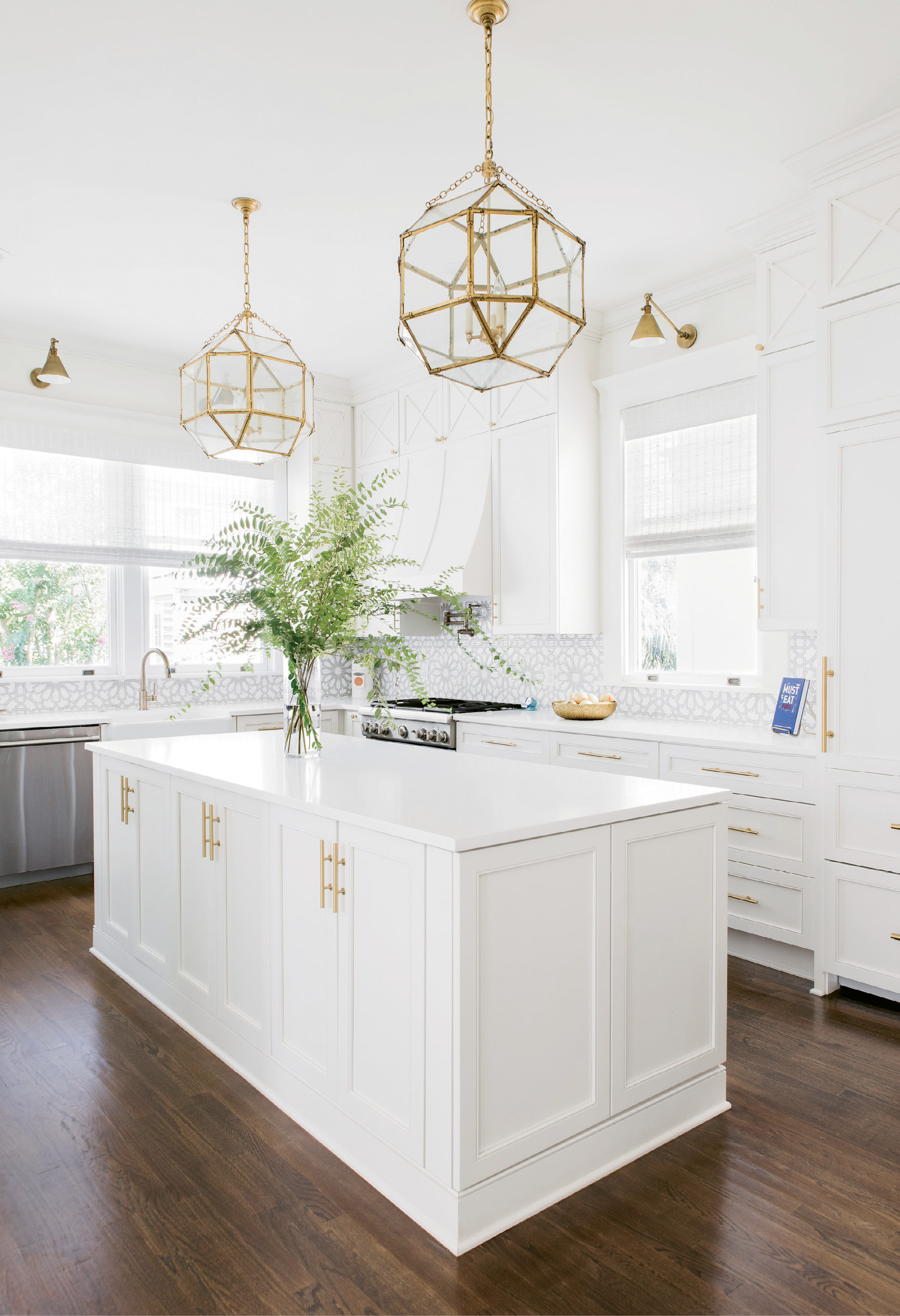 """LIGHT & BRIGHT: """"The kitchen is a good example of what Melissa did so well, filling every nook and cranny and making them useful in some way,"""" says Alison. Fireclay backsplash and gold pendants and sconces add glamour to the utilitarian space."""