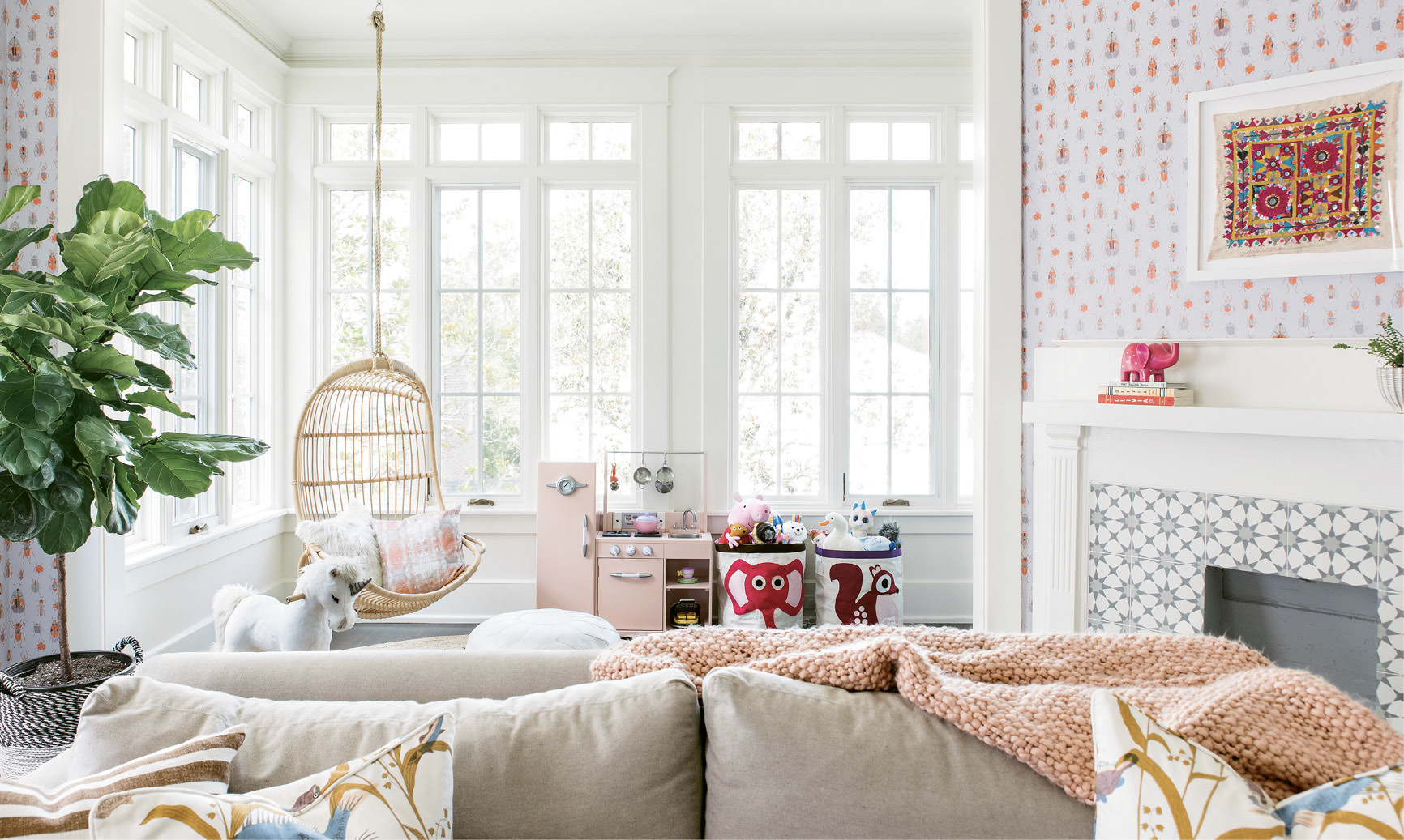 """In the vibrant playroom, comfy, kid-friendly furniture—like the Serena & Lily hanging chair and Lee Industries pullout sofa outfitted in performance fabric—mix with playful décor, including a vintage textile interior designer Melissa Lenox found in Jodhpur, India, and Lulie Wallace's """"Meyers"""" wallpaper."""