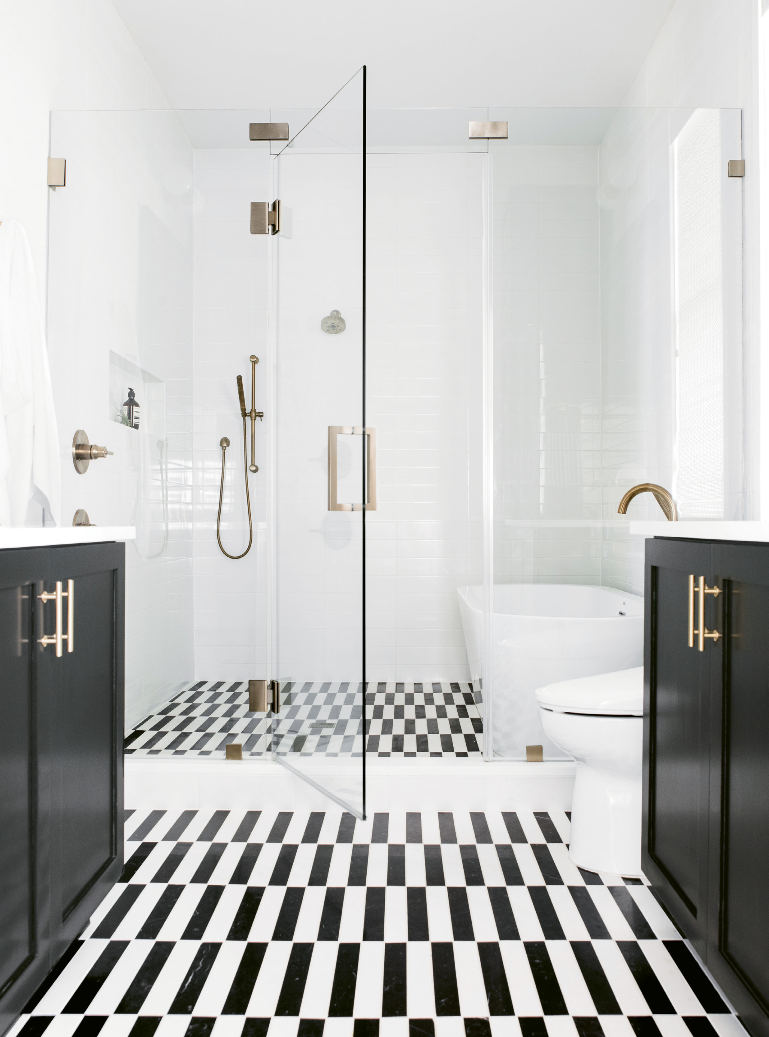 """CLEAN & SERENE: The master suite rivals boutique hotels for its comfort and style. A space-saving """"wet room"""" configuration in the bath fits a walk-in shower and soaking tub, while glistening white-tile walls, cabinets covered in Benjamin Moore's """"Black Beauty,"""" and a custom-cut marble tile floor add drama."""