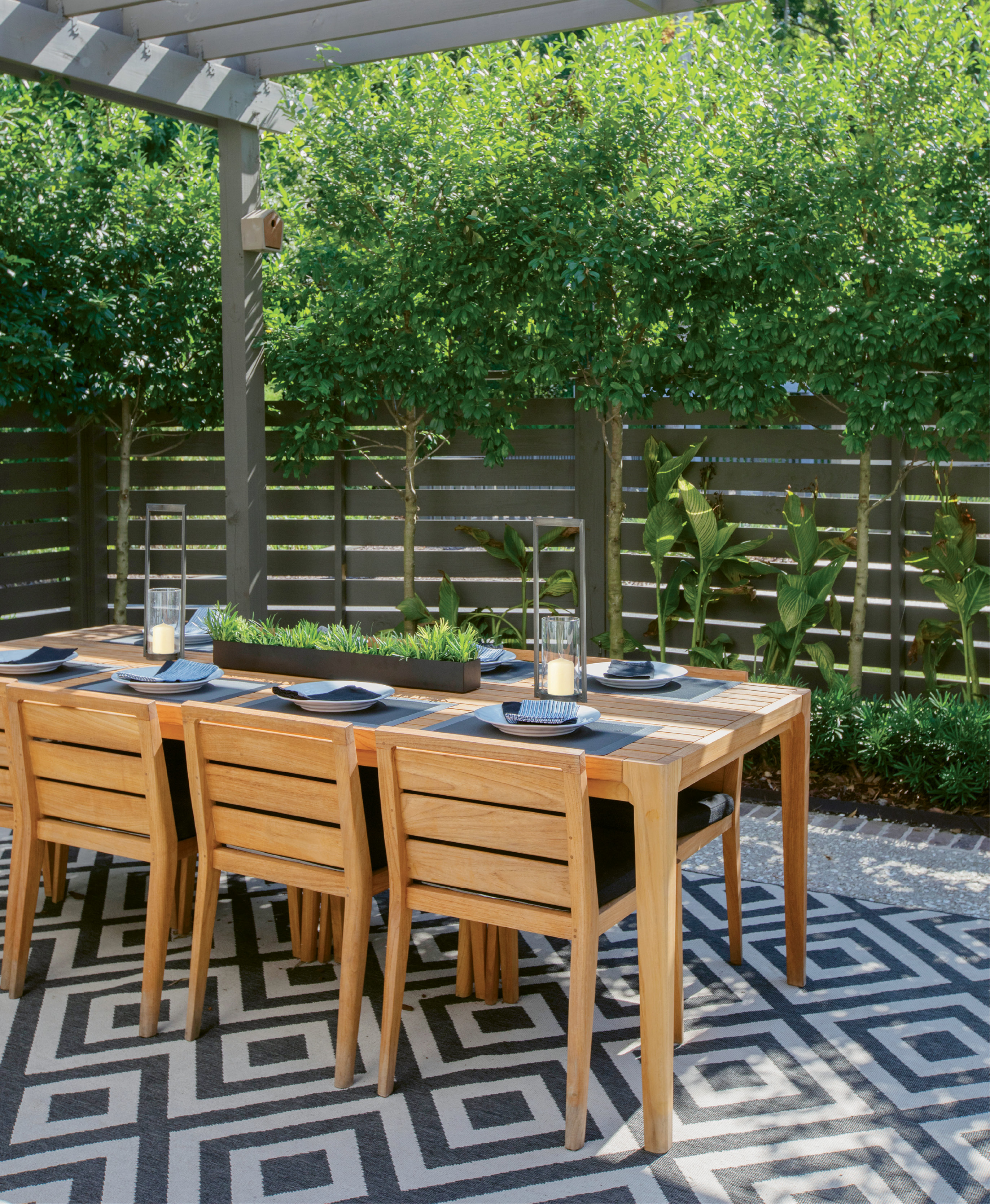 Limbed holly bushes soften a horizontal wood-slat fence, providing privacy as well as filtered light for the Thomae family's alfresco dining room.