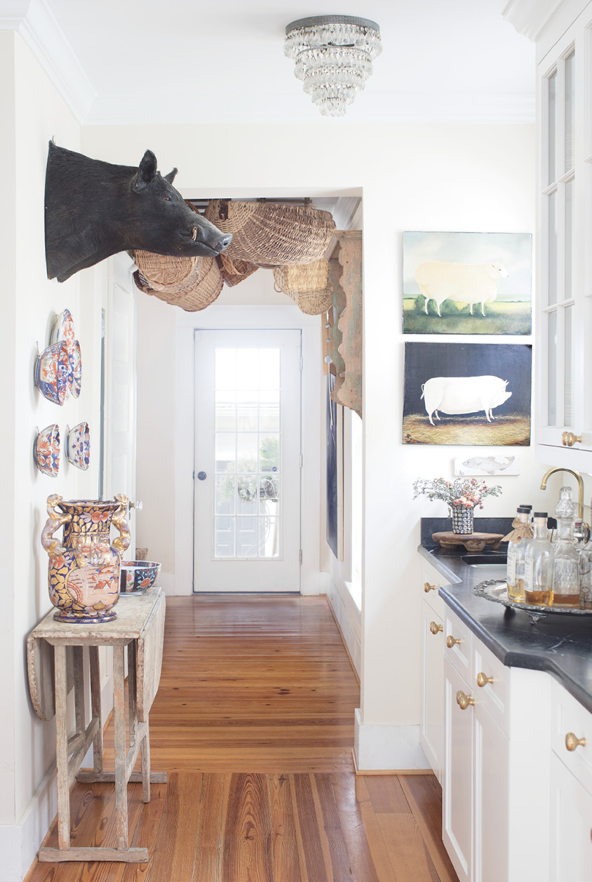 In the sunlit hallway off the butler's pantry, Renee the taxidermy boar (an estate sale score and Father's Day gift to Mel from the kids) oversees collections of baskets and antique Imari porcelain.