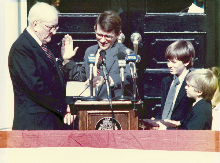 """Mayor Riley has taken the oath of office a record 10 times. He's pictured here in 1984 (his third term), with his father, Joseph P. Riley, Sr., administering the oath, and his sons, Joseph and Bratton (far right), by his side. When Joe III did the honors for his father in January 2012, he inserted some humor by beginning the oath with, """"So, for the last time…."""""""