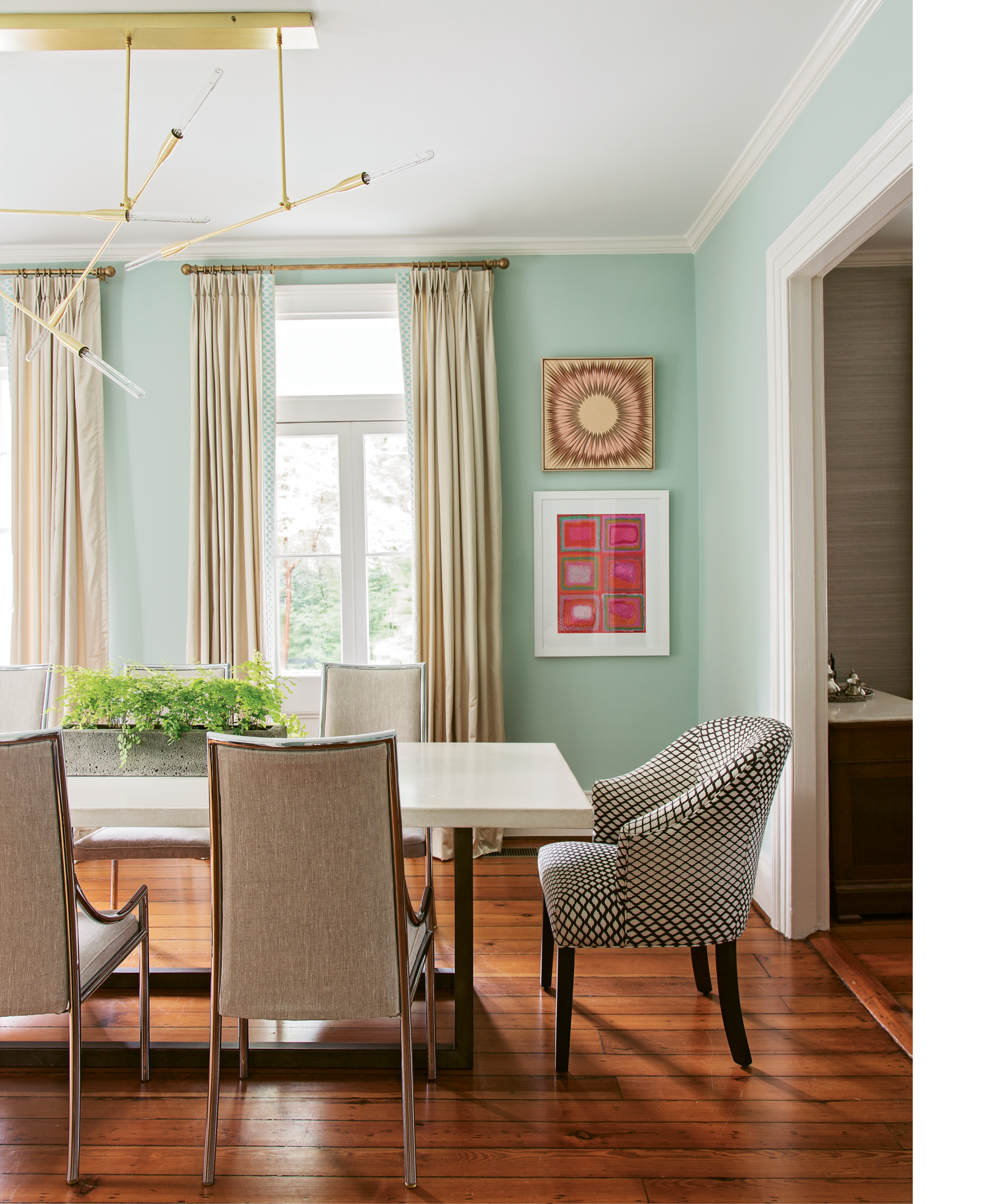 BALANCING ACT: In the formal dining room, a sleek concrete table and chrome-edged chairs ground sea-green walls and colorful artwork, such as this framed textile scored at High Point Market (top) and painting by area artist Linda Elksnin (bottom).