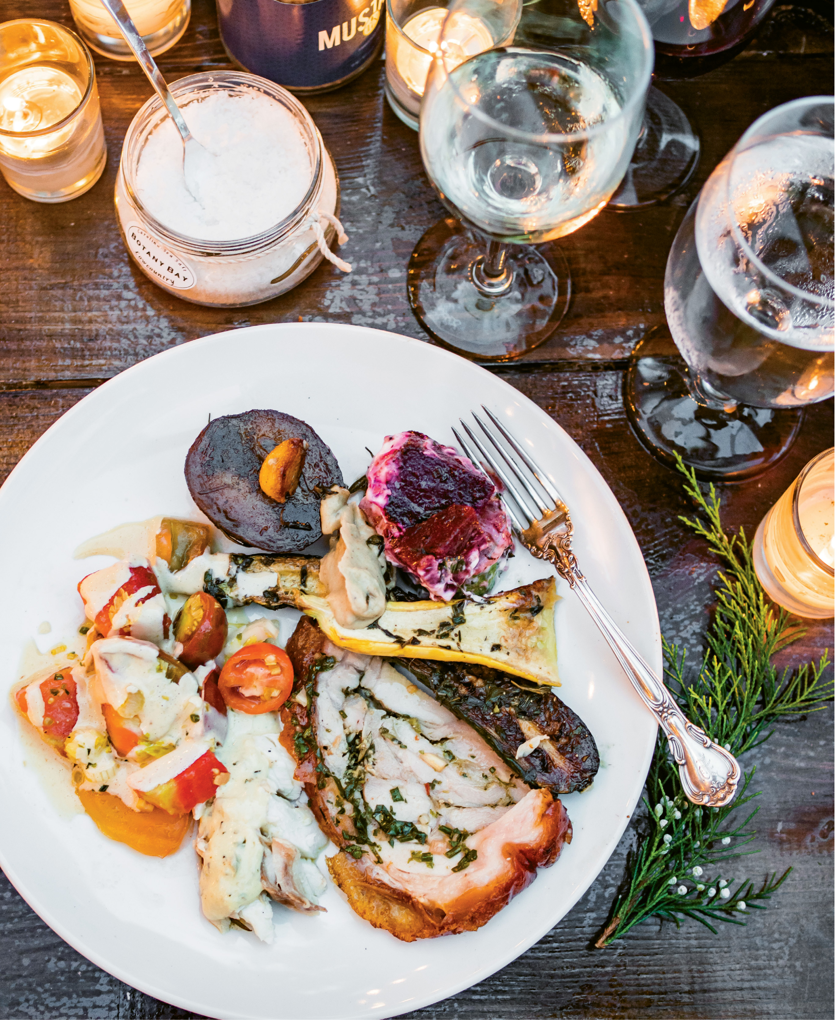 A plateful of fire-roasted delights, including porchetta, snapper, and veggies, is complemented by a cool heirloom  tomato salad.