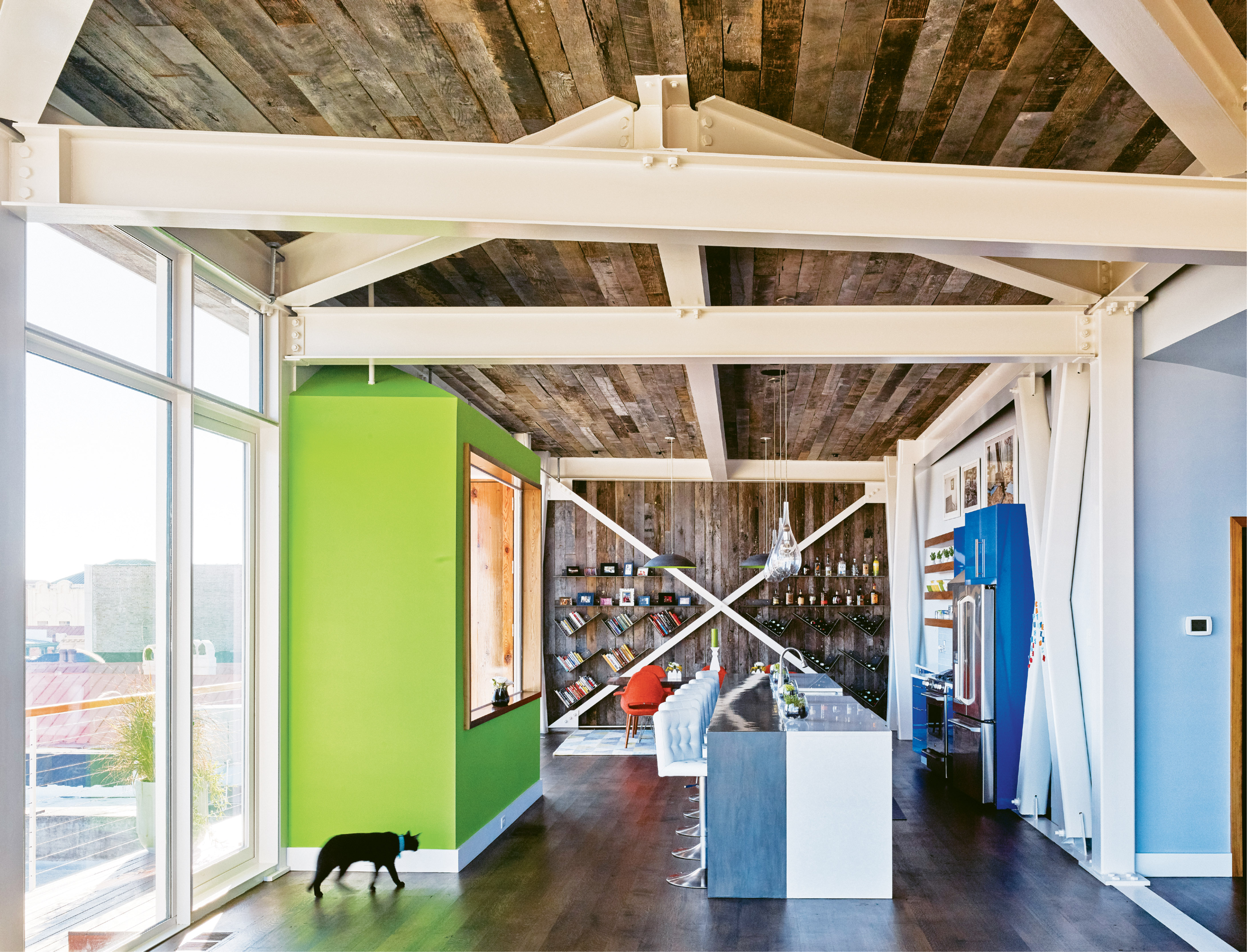 "Yessian gravitates toward bright colors. He painted an accent wall in Sherwin Williams's ""Outrageous Green;"" the same bold hue graces the underside of the dome lights above the dining table. Made by furniture designer Ben K. Mickus and sourced on Etsy, the pendants are fashioned from repurposed carbon-steel woks."