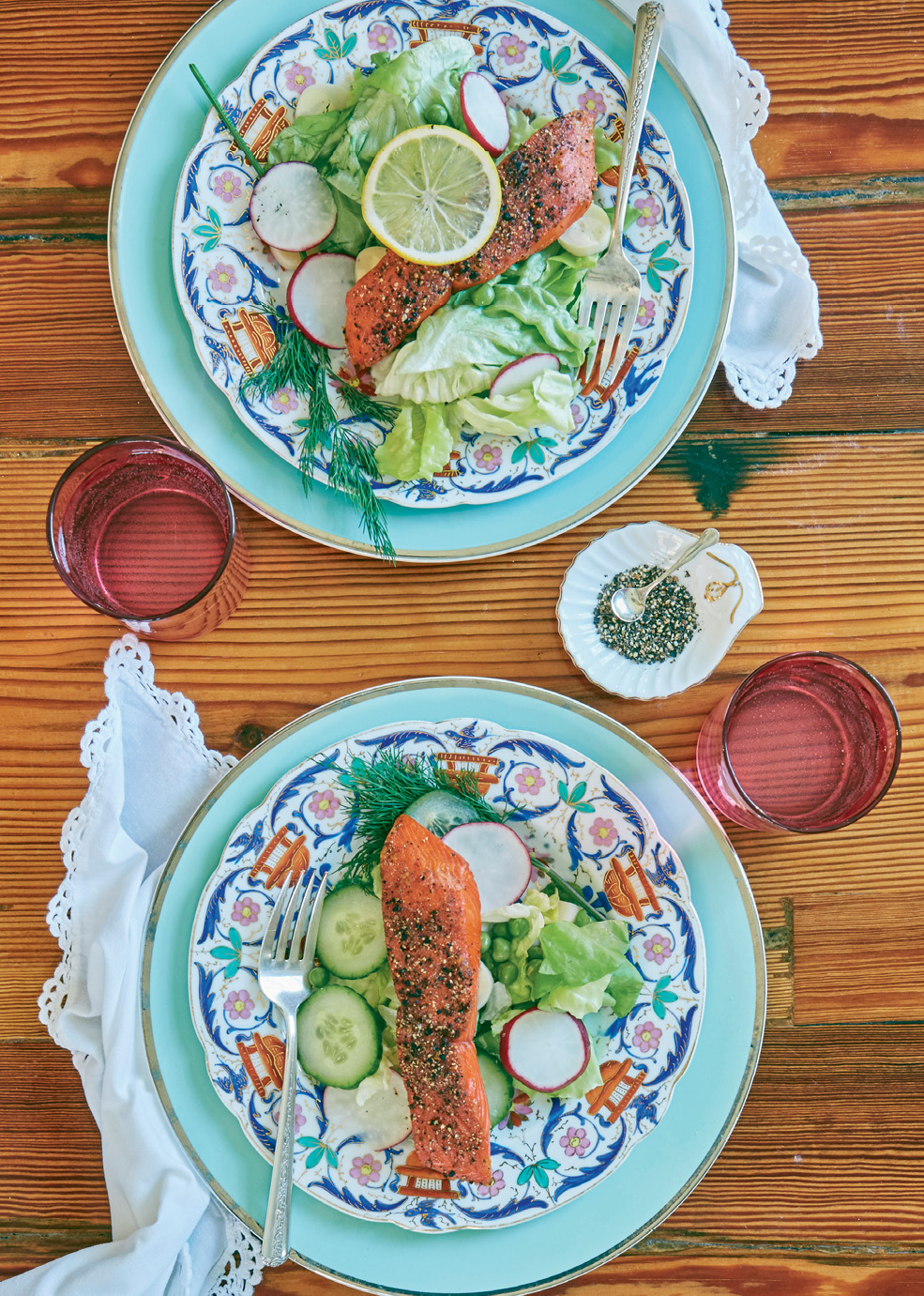 Salmon steaks are grilled skin-side up, making them a juicier addition to the greens.