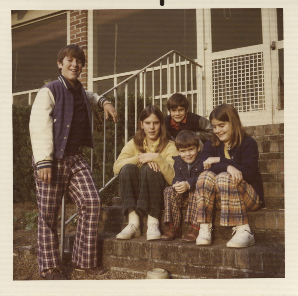 Julian standing with four of his siblings on the steps of their North Shore Drive home