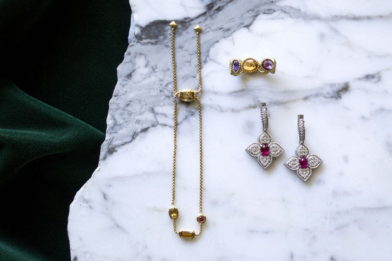 """(Clockwise from top right) 18K gold and 6.36 ct. multi-sapphire eternity band, $3,100 at Croghan's Jewel Box; David Yurman 18K Novella chain bracelet, $1,350 at REEDS Jewelers; 18K white-gold diamond """"Ruby Princess"""" flower earrings, $8,500 at Roberto Coin; David Yurman 18K gold Novella chain bracelet, $1,350 at REEDS Jewelers"""