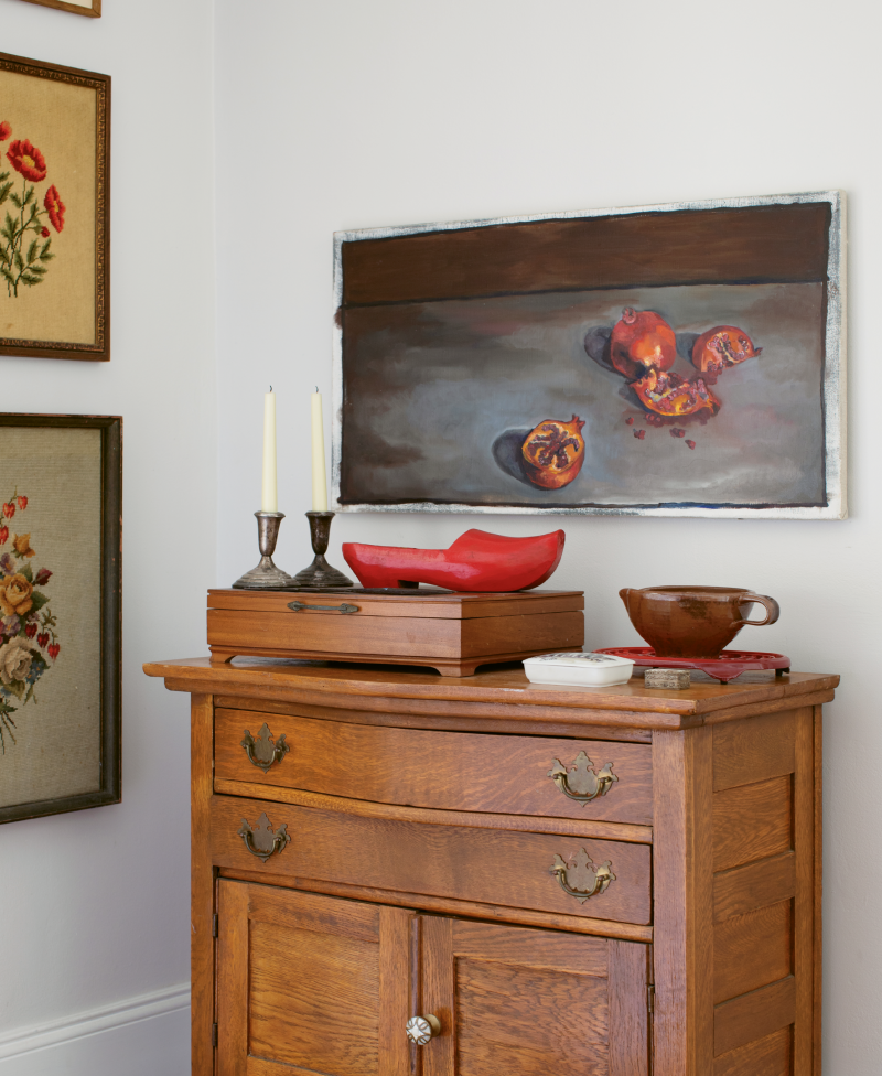 Jacques and Carrie Larson's West Ashley home looks contemporary from the curb, but it's filled with meaningful pieces from the past and present, like this pomegranate still-life by Carrie, needlepoints by Jacques's grandmother, and a red clog carved by his great-grandfather.