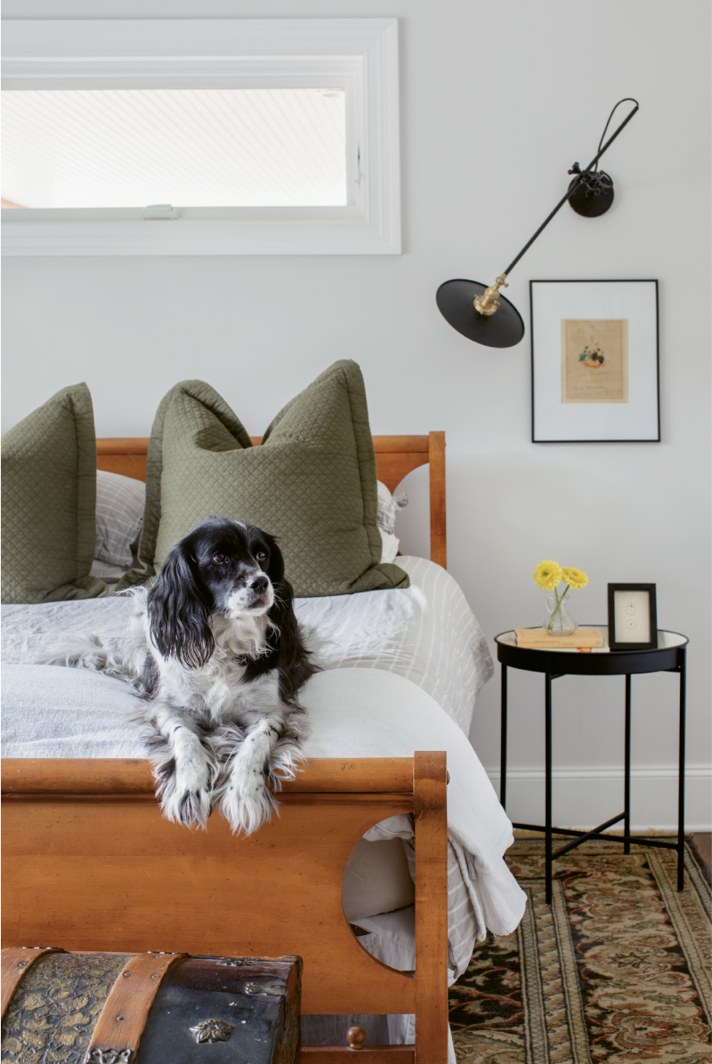 MIX, MASTERED: In the couple's bedroom, a hand-me-down rug helps establish a color palette of earthy neutrals and olive greens; black accents, such as the sconce by Workstead, keep things grounded.