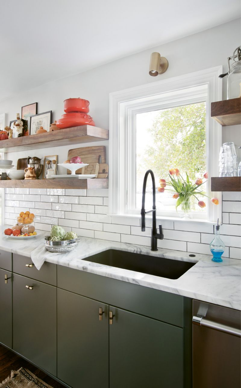 """WHERE THE MAGIC HAPPENS: Thanks to the removal of a wall between the kitchen and living room, cooking for guests is no longer claustrophobic. The refreshed space makes good use of local materials, including the faucet from Molufs and painted concrete backsplash from Palmetto Tile. """"Tile can really make a space without being too distracting,"""" Carrie notes. Quartzite countertops, flat-face cabinets, and hardware from Anthropologie add to the clean look, while a rotating display of objects provides the finishing touch. """"We love the open shelves, and I find I'm always rearranging and shuffling things around; it is really inspiring to see fresh produce and artwork in the kitchen,"""" she continues."""