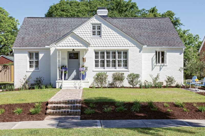 """FRESH FACED: To camouflage brick patchwork and better blend the scallop detailing with the rest of the façade, homeowner Rachel Levkowicz had the exterior coated in Benjamin Moore's """"White Dove,"""" using Sherwin Williams' """"African Gray"""" as an accent hue. Other Side of the River constructed the property's new walkway. """"It's one of my favorite things I added to the house,"""" says Rachel."""