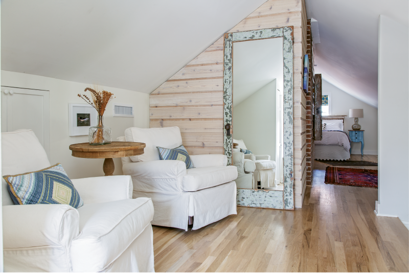 ABOVE & BEYOND: The second floor houses a relaxing master suite. Dimmable recessed lighting; comfy upholstered chairs from Celadon; and textural elements such as cedar planks, a Past to Present Décor mirror made from salvaged wood, and exposed brick amp up the space's homey vibe.