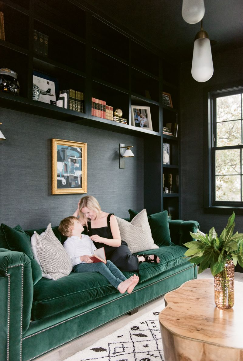 "Molly and Sawyer read in the library, where the Phillip Jeffries ""Manila Hemp"" wallpaper in ""charcoal"" and Hickory Chair sofa upholstered in emerald-green velvet by Ralph Lauren set a moody, masculine tone."