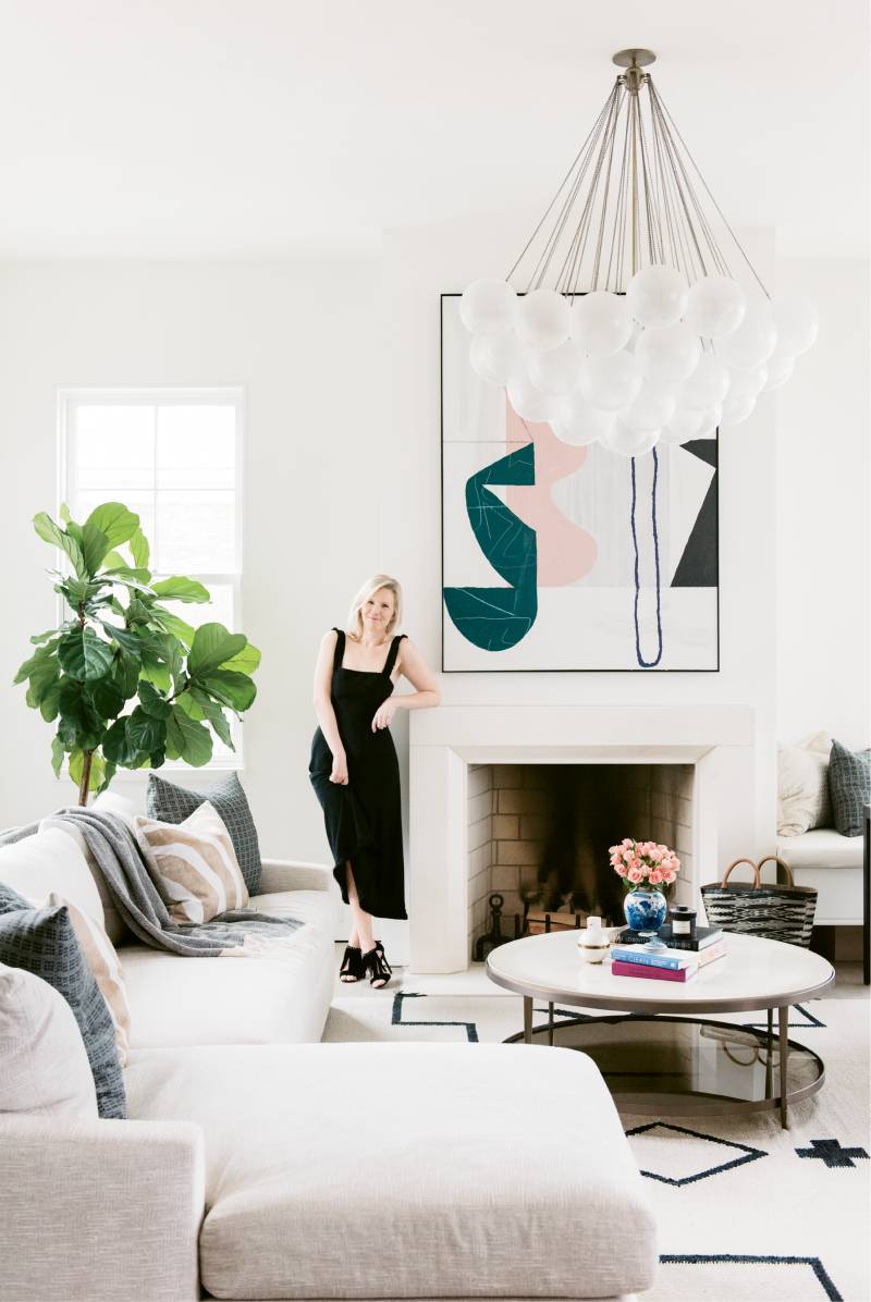 "Molly Fienning in the living room near an abstract painting by Brian Coleman; ""I fell in love with his work at the George Gallery downtown, so we commissioned him to create sister paintings that complement one another,"" she says."