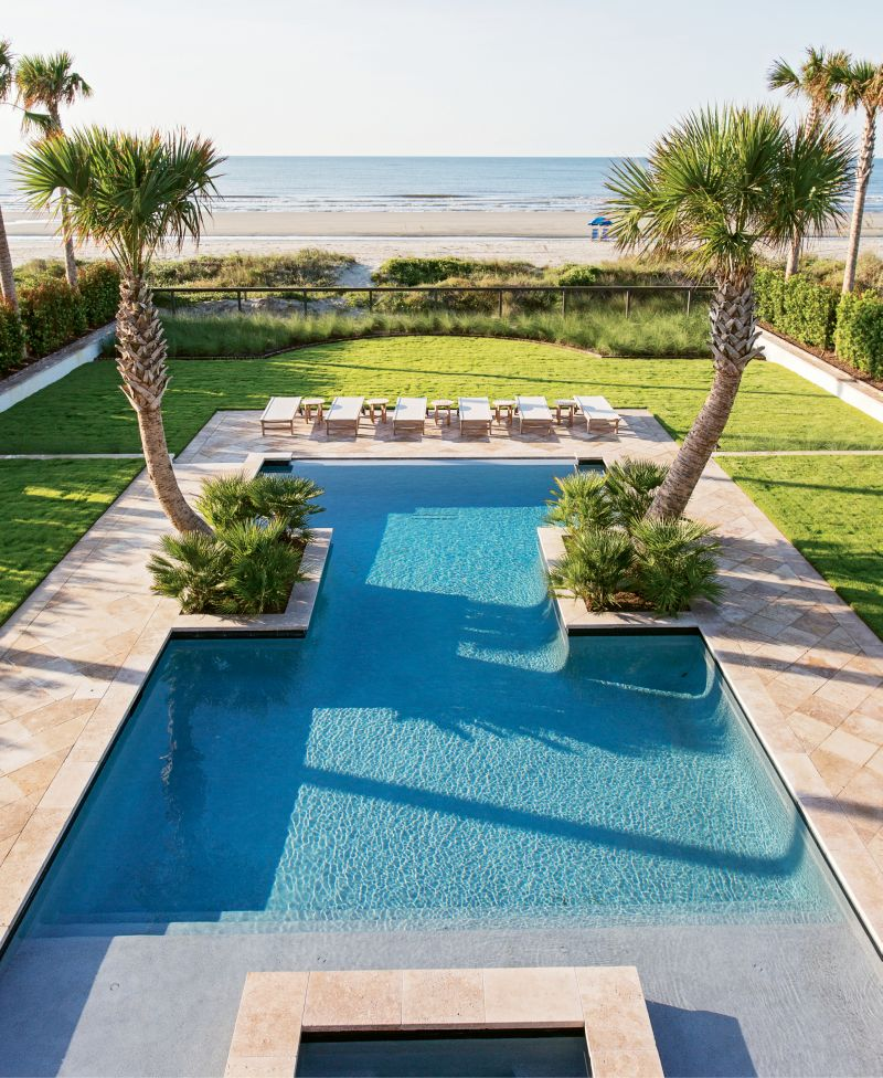 An I-shaped pool, mirror-image palmetto trees, and luxe Kingsley Bate patio loungers mean the Lamachs' own yard provides a view that rivals the nearby ocean.