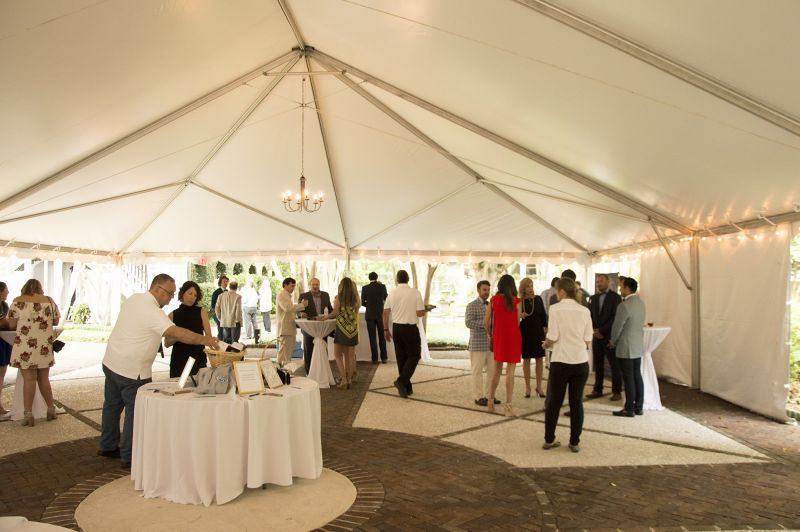 Guests mingled amid bidding tables, music, food, and beverages beneath the main tent.