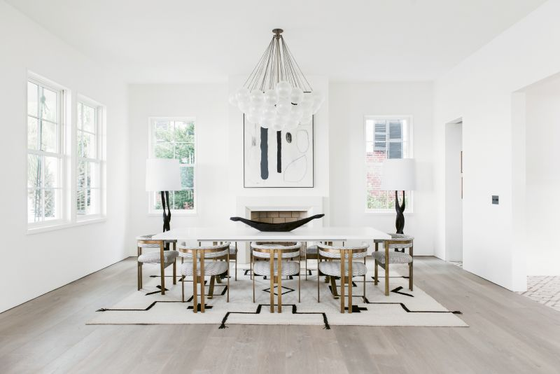 "In the dining room, sculptural elements such as the Apparatus ""Cloud"" light fixture, Kelly Wearstler dining chairs, and a custom Merida rug woven with leather straps are like functional works of art."