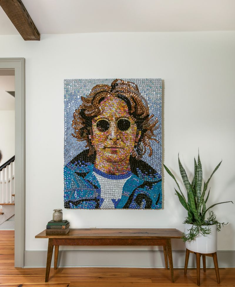 The couple kept the decor minimal in order to highlight the architectural features, but the accessories they do have pack plenty of personality. After admiring the work of local artist Molly B. Right for many years, the Ellsworths commissioned this bottle-cap portrait of John Lennon, which hangs above a custom Landrum table in the living area.