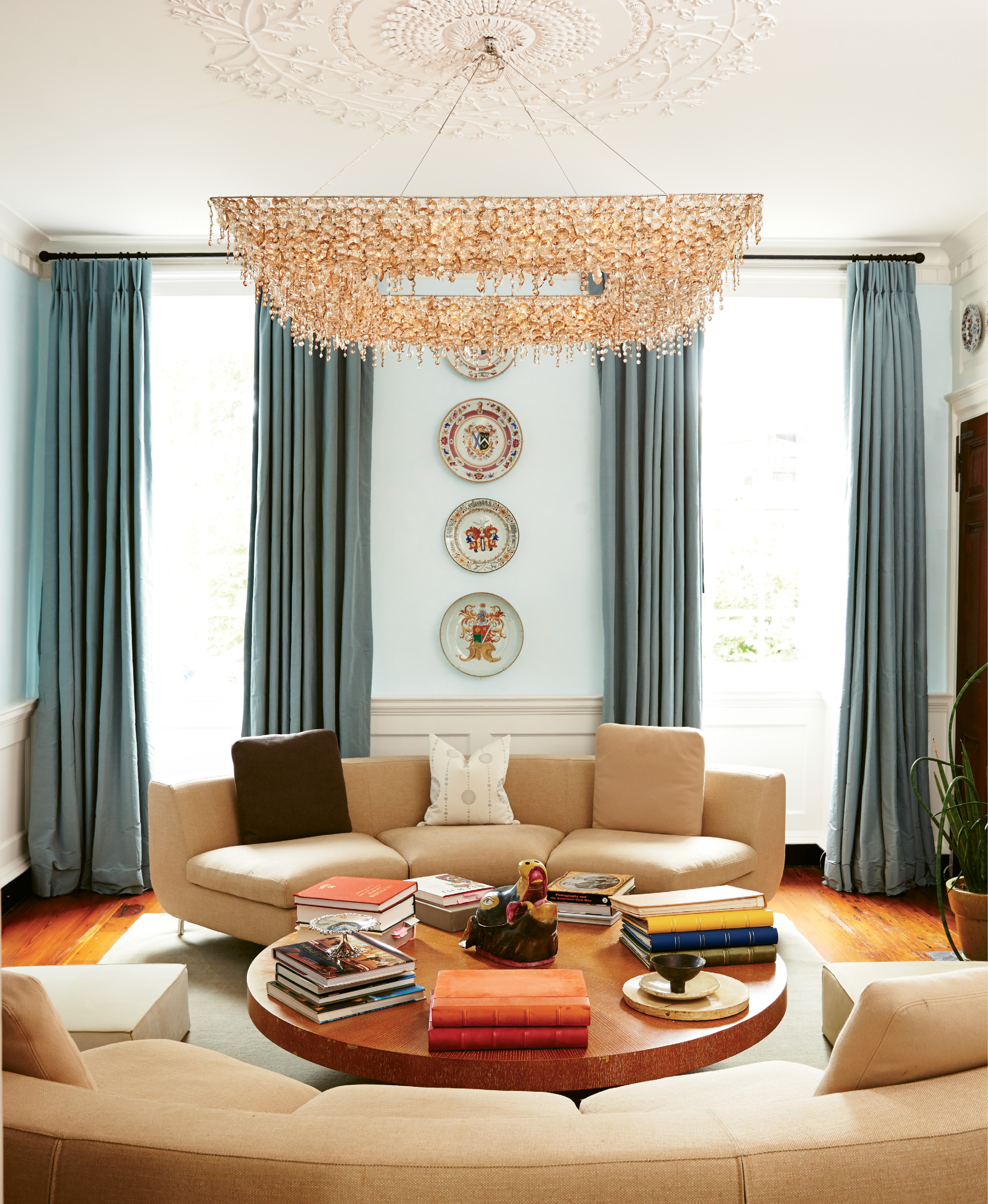 HIGH, LOW, & IN BETWEEN: The Pollaks enlisted jewelry designer and friend James de Givenchy to help them choose décor in keeping with their eclectic personal style. In the living room, a glittering chandelier and Suzanne's collection of 18th-century Chinese porcelain keep company with a coffee table from Crate & Barrel.